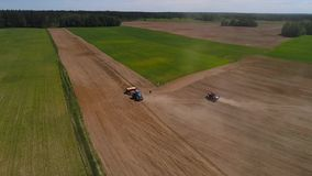 Aerial drone shot of a two tractors seeding a field. One tractor stops beside another. HD stock video