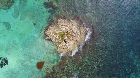 Aerial drone shot. A view of the coral island from a bird`s eye view. The camera looks down and rotates slowly. Turquoise water of the Caribbean Sea. Cancun stock footage