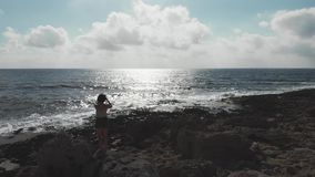 Aerial drone shot woman with phone camera standing on rocky beach taking pictures of sun road and horizon sea ocean. Seashore with. Female making photos stock video