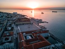 Drone sunset photo - Alfama District and the Comercio Square of Lisbon, Portugal. Aerial drone sunset photo - Colorful orange roofs of the Alfama district & the stock photography
