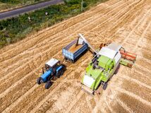 Free Aerial Drone Top View Big Powerful Industrial Combine Harvester Machine Unloading Bin Of Wheat Cereal In Tractor On Field Bright Royalty Free Stock Images - 195075099