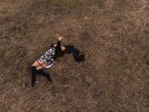 Aerial drone top view of a girl lying in a field relaxing and dancing. Wearing a dress with stockings stock photo