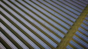 Solar energy panels, drone fly over. Aerial drone video footage looking down and flying diagonally above rows of solar energy panels in a rural solar farm stock footage