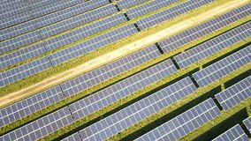 Solar panels and renewable energy farm. Aerial drone video footage looking down onto rows of solar panels in a renewable energy farm in the English countryside stock footage