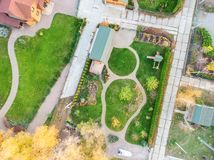 Aerial drone view of backyard garden with circle wath path, green grass lawn and trees. Landscape design and gardening stock photo