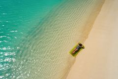 Aerial drone aerial view of Beautiful girl having fun on the sunny tropical beach. Seychelles.  stock photography
