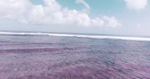 Aerial view of beautiful waves against sky. Aerial drone view of beautiful ocean waves with white water foam against cloudy sky - colored video in slow motion stock video