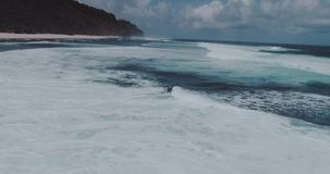Aerial view of beautiful waves against sky. Aerial drone view of beautiful ocean waves with white water foam against cloudy sky - video in slow motion stock video