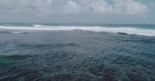 Aerial view of beautiful waves against sky. Aerial drone view of beautiful ocean waves with white water foam against cloudy sky - video in slow motion stock video footage