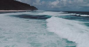 Aerial view of beautiful waves against sky. Aerial drone view of beautiful ocean waves with white water foam against cloudy sky - video in slow motion stock footage