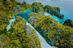 Aerial drone view beautiful shallow tropical Big and Small Lagoon explored inside by tourist on kayaks surrounded by. Jagged limestone karst cliffs. El Nido royalty free stock image