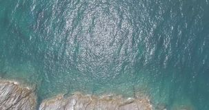 Aerial view of sea waves crashing on rocks of tropical island. Aerial drone view of beautiful waves and sea shore cliff with green palms stock video footage