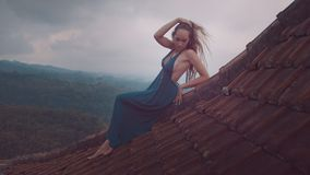 Aerial drone view of beautiful woman in long blue dress sitting on tiled red roof of the house against amazing mountain view and c Royalty Free Stock Photos