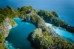 Aerial drone view of Big lagoon surrounded by jagged limestone karst cliffs in morning soft light just before tourist. Arrive. El Nido, Palawan Philippines royalty free stock image