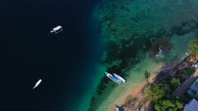 Aerial drone view of boats anchored in the bay with clear and turquoise water. Fishing and transport vessels are in port or dock. Transport boats for stock footage
