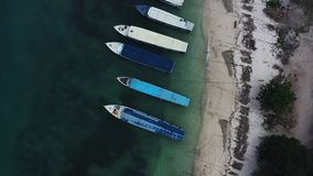 Aerial drone view of boats anchored in the bay with clear and turquoise water. Fishing and transport vessels are in port or dock. Transport boats for stock video
