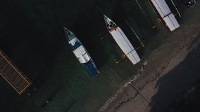 Aerial drone view of boats anchored in the bay with clear and turquoise water. Fishing and transport vessels are in port or dock. Transport boats for stock video footage