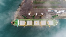 Aerial drone view of cargo ship and cranes in morning fog in the harbor. Sea port Varna, Bulgaria.  stock video footage