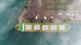 Aerial drone view of cargo ship and industrial cranes in fog in the sea harbor. Varna city, Bulgaria stock video footage
