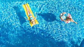 Aerial drone view of children in swimming pool from above, happy kids swim on inflatable ring donuts, girls have fun in water. On family vacation royalty free stock photography
