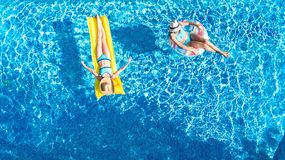 Aerial drone view of children in swimming pool from above, happy kids swim on inflatable ring donuts, girls have fun in water. On family vacation stock photo