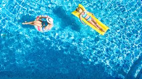 Aerial drone view of children in swimming pool from above, happy kids swim on inflatable ring donuts, girls have fun in water. On family vacation royalty free stock photo