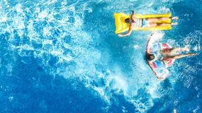 Aerial drone view of children in swimming pool from above, happy kids swim on inflatable ring donuts, girls have fun in water. On family vacation royalty free stock image