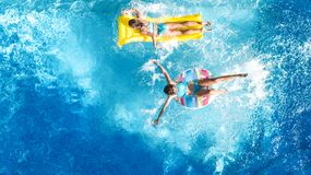 Aerial drone view of children in swimming pool from above, happy kids swim on inflatable ring donuts, girls have fun in water. On family vacation stock photos