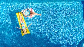 Aerial drone view of children in swimming pool from above, happy kids swim on inflatable ring donuts, girls have fun in water. On family vacation royalty free stock photos