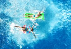 Aerial drone view of children in swimming pool from above, happy kids swim on inflatable ring donuts, girls have fun in water. On family vacation royalty free stock images