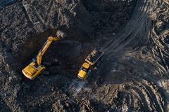 Aerial drone view of excavator loading the tipper truck royalty free stock image