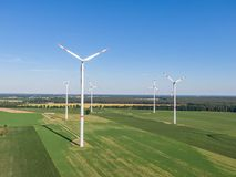 Aerial drone view of five wind power turbines, part of a wind farm, on a green field in eastern Germany near the city of Cottbus. Aerial drone view of five wind royalty free stock photography