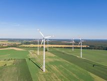 Aerial drone view of five wind power turbines, part of a wind farm, on a green field in eastern Germany near the city of Cottbus. Aerial drone view of five wind stock image