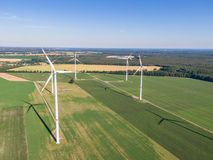Aerial drone view of five wind power turbines, part of a wind farm, on a green field in eastern Germany near the city of Cottbus. Aerial drone view of five wind stock photo