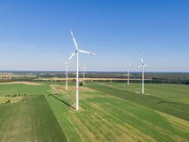 Aerial drone view of five wind power turbines, part of a wind farm, on a green field in eastern Germany near the city of Cottbus. Aerial drone view of five wind stock photos