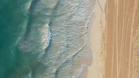 Aerial drone view flying over azure waves and sand beach, no people