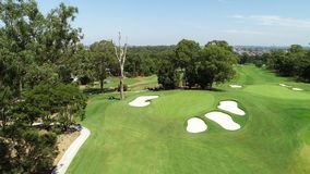 Aerial drone view golf course green with sand bunkers, flag, trees, green grass against blue sky. Aerial drone view of golf course green with sand bunkers, flag royalty free stock image