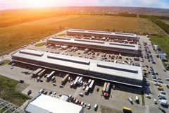 Aerial drone view of group of large modern industrial warehouse or factory buildings in suburban city area.Logistic transportation