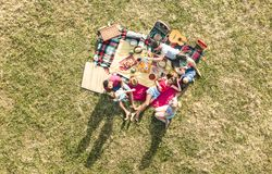 Aerial drone view of happy families having fun with kids at picnic. Barbecue party - Multiracial love concept with people playing with children at park stock photography