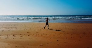 Aerial Drone View Of Healthy Sportive Woman Running On Beach Stock Photography