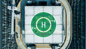 Aerial drone view of helipad on the roof of a skyscraper iin downtown with cityscape view on sunny day royalty free stock photo