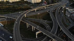 Aerial drone view of highway multi-level junction road with moving cars at sunset. Cars are moving on a multi-level road stock video footage