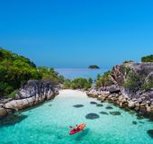 Aerial drone view of in kayak in crystal clear lagoon sea water during summer day near Koh Lipe island in Thailand. stock photo