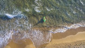 Aerial drone view of kids playing with an inflatable on a beach and sea in Corfu Greece. royalty free stock image