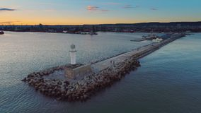 Aerial drone view of lighthouse at sunset in Varna seaport, Bulgaria.  stock footage