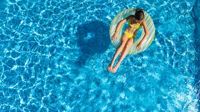 Aerial drone view of little girl in swimming pool from above, kid swims on inflatable ring donut , child has fun in blue water stock photos