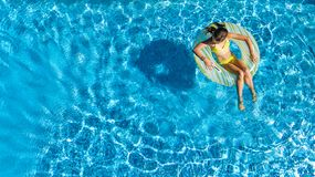 Aerial drone view of little girl in swimming pool from above, kid swims on inflatable ring donut , child has fun in blue water stock images