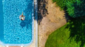 Aerial drone view of little girl in swimming pool from above, kid swims on inflatable ring donut , child has fun in blue water royalty free stock image