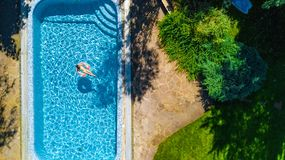 Aerial drone view of little girl in swimming pool from above, kid swims on inflatable ring donut , child has fun in blue water royalty free stock photography