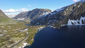 Aerial drone view mountain road by the lake in Norway. Scandinavian journey with beautiful landscape stock video footage